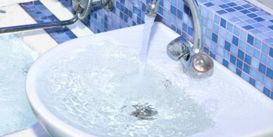 An overflowing sink and bathtub.