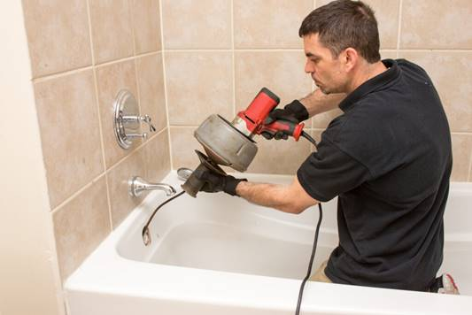 A Milani technician clearing a bathtub drain.